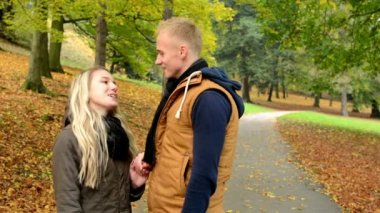 Young model couple in love - man suddenly kisses a woman - autumn park(nature) - (man and woman) couple talking in park - happy couple — Stock Video