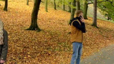 Young model couple in love - happy couple in autumn park(nature) - woman on phone and man on phone (couple calling by smartphone) - concept (man and woman are look for) - dating - couple holding hands — Stock Video