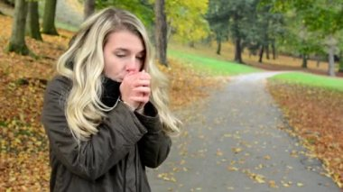 Woman shivers with cold - woman gets warmer - autumn park (nature) - woman portrait — Stock Video