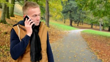Man on the phone (man calling by smartphone) - man smiles (happy) - man in autumn park (nature) — Stockvideo