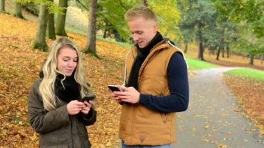 Young model couple in love - autumn park(nature) - couple (man and woman) relax in park - happy couple - woman on phone and man on phone (write message) - happy couple smile — Stock Video