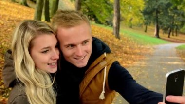 Young model couple in love - autumn park(nature) - man and woman are photographing  by smartphone (selfie) - happy couple - couple kiss — Stock Video