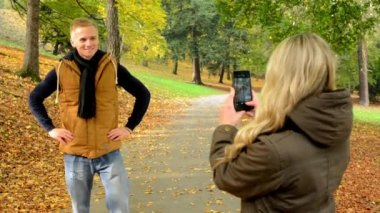 Young model couple in love - autumn park(nature) - woman photographing man with smartphone - happy couple — Stock Video
