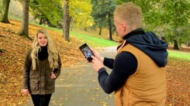 Young model couple in love - autumn park(nature) - man photographing woman with smartphone - happy couple — Stock Video