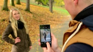 Young model couple in love - autumn park(nature) - man photographing woman with smartphone - happy couple - closeup — Stock Video