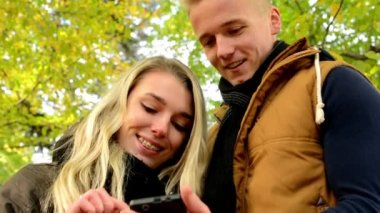 Young model couple in love - autumn park(nature) - happy couple on smartphone - man shows something woman on smartphone — Stock Video