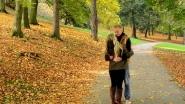 Young model couple in love - autumn park(nature) - couple (man and woman) walking in park - couple holding hands - woman runs to man - couple kiss - couple embrace - happy couple — Stock Video