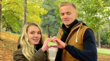 Young model couple in love - autumn park(nature) - happy couple - couple forms a heart with their hands — Vídeo de Stock