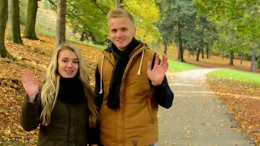 Young model couple in love - autumn park(nature) - couple wave with hands - happy couple — Stock Video