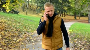 Man on the phone (man calling by smartphone) - man walking in autumn park - man smiles (happy) — Stockvideo