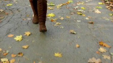 Woman walking in autumn park - shot on feet - pavement with leaves — Vídeo Stock