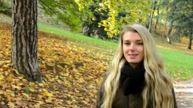 Woman walking in autumn park - woman smiles (happy) — Vídeo de Stock