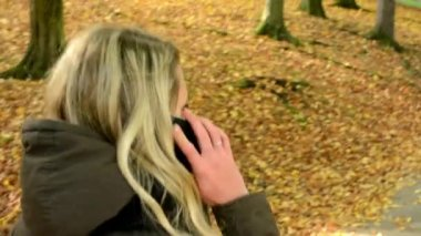 Woman on the phone (woman calling by smartphone) - woman walking in autumn park - shot from back — Vídeo de Stock