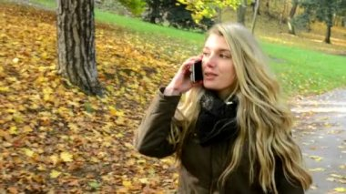 Woman on the phone (woman calling by smartphone) - woman walking in autumn park - woman smiles (happy) — Stockvideo
