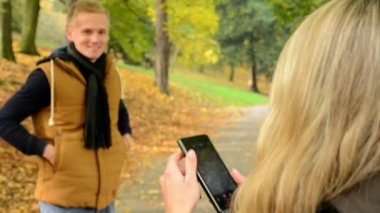 Young model couple in love - autumn park(nature) - woman photographing man with smartphone - happy couple - closeup — Stock Video
