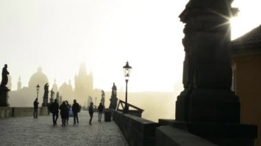 Charles bridge with people - sunrise - city - morning mist - buildings with statues — Stock Video