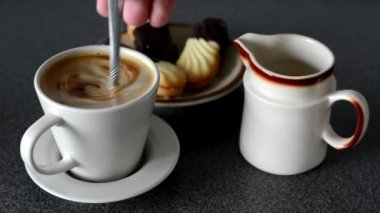 Coffee with milk - sweets (cookies) - stir coffee with spoon — Stock Video
