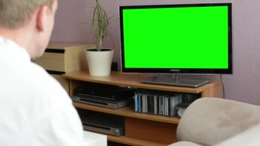 Man watches TV(television) - green screen — Stock Video