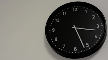 Black clock on the white wall — Stock Video