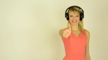 Young attractive woman listens to music with headphones and shows a thumb up to the agreement - studio — Stok video