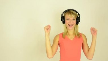 Young attractive woman listens to music with headphones and rejoices - studio — Stock Video