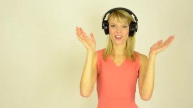 Young attractive woman listens to music with headphones and woman is surprised - studio — Stock Video
