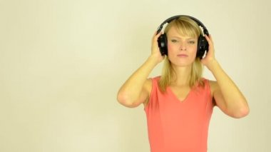 Young attractive woman listens to music with headphones - horrible music- studio — Stock Video