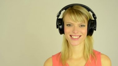 Young attractive woman listens to music with headphones and smiles - studio — Stock Video