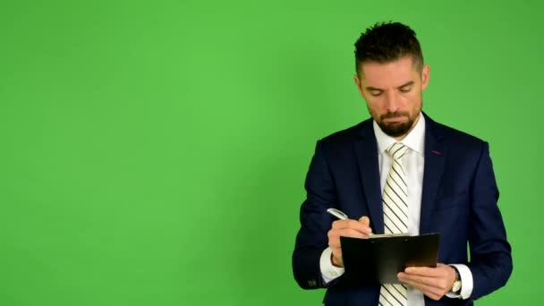 Business man writes to paper (serious face) - green screen - studio — Vídeo de stock
