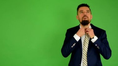 Business man adjusts his tie - green screen - studio — Stock Video