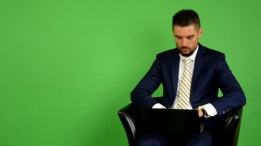 Business man sits and works on notebook and smiles - green screen - studio — Stock Video