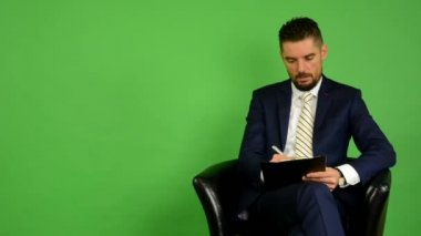 Business man sits and writes to paper and smiles - green screen - studio — 图库视频影像