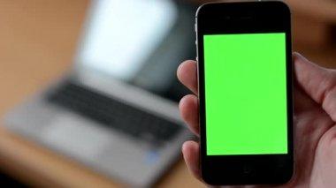 Smartphone green screen - computer (laptop) in background — Stock Video