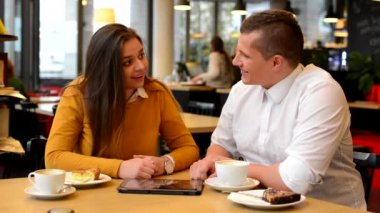 Happy couple works on tablet in cafe - coffee and cake — 图库视频影像