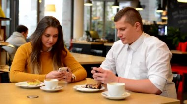 Man works on mobile phone and woman works on smartphone in cafe - coffe and cake — 图库视频影像