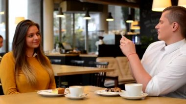 Man photographing woman with smartphone in cafe - coffee and cake — Video Stock