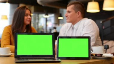 Computer (notebook) and tablet green screen - happy couple smiles to camera and point at notebook in cafe - happy couple talk - coffee and cake — Stock Video
