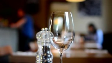 Restaurant - empty wine glasses with salt cellar - people in background — Stock Video
