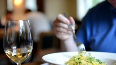 Restaurant - man eats spaghetti - wine - people in background — Stock Video
