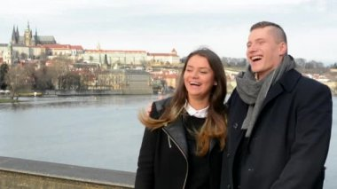 Happy couple laugh and talk (conversation) - bridge - city (Prague) in background — Stock Video
