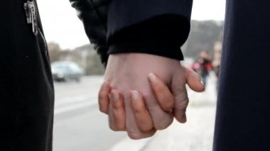Young model couple in love - couple holding hands (closeup) - urban street with cars and people in background — Stock Video
