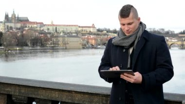 Man works on tablet on the bridge - city (Prague) in background — Stok video