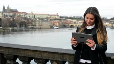 Woman works on tablet on the bridge - city (Prague) in background — Stok video