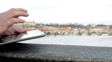 Man works on tablet on the bridge - city (Prague) and river in background - closeup (shot on hand) — Stok video