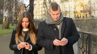 Couple walk in city and work on smartphone — Stok video