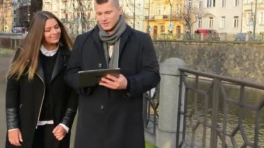 Happy couple work on tablet and walk in city — Stok video