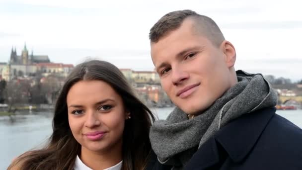 Young happy couple in love kiss and smile to camera - city (Prague) in background - closeup — Vidéo