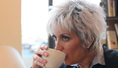 Business middle aged woman drinks coffee - closeup (detail) from side — Stok video