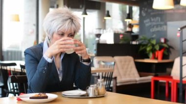 Business middle aged woman drinks coffee in cafe and smiles to camera — Stok video