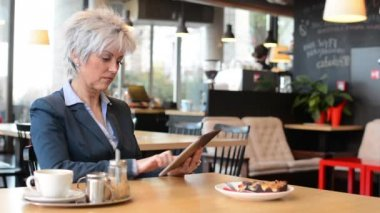 Business middle aged woman works on tablet in cafe - coffee and cake — Stok video